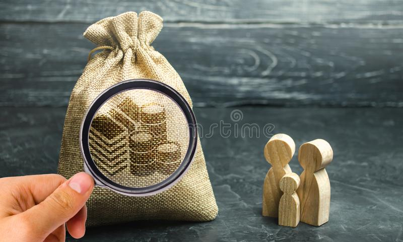 De miniatuur houten tribune van familiebeeldjes dichtbij een geldzak Het concept besparingen Begroting planning Distributie van w royalty-vrije stock foto