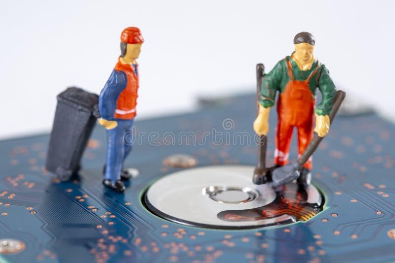 De miniatuurarbeiders die een gebroken harde aandrijving schoonmaken en recycleren het stock afbeeldingen