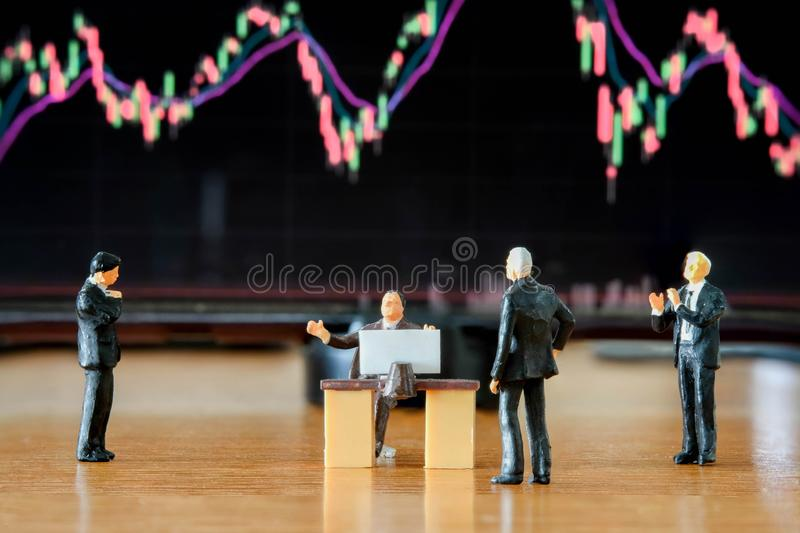 De miniatuurfiguur zakenmensen of de vergadering van de Handelaar van de Beurs en het raadplegen voor de Grafiek van de Voorraad  stock fotografie