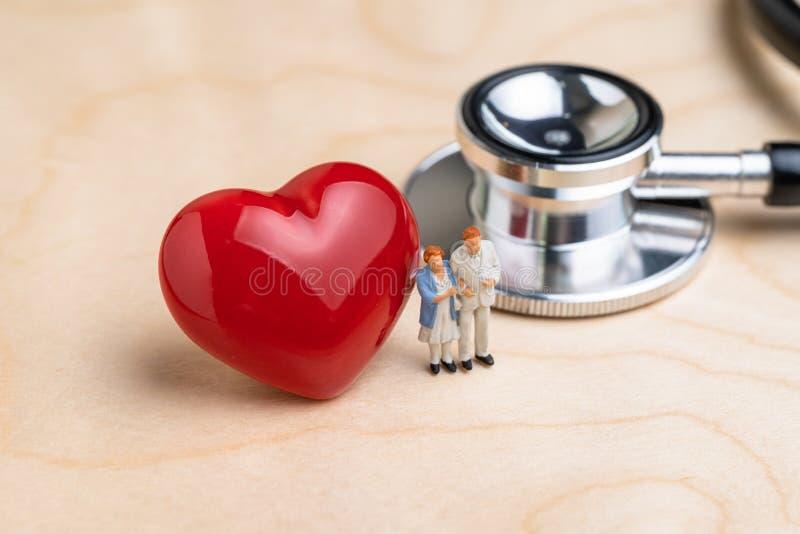 De miniatuurmensen bejaarde oudste trok paar met de stethoscoop van de arts en shinny rood hart op houten lijst, gezondheidszorg  royalty-vrije stock fotografie