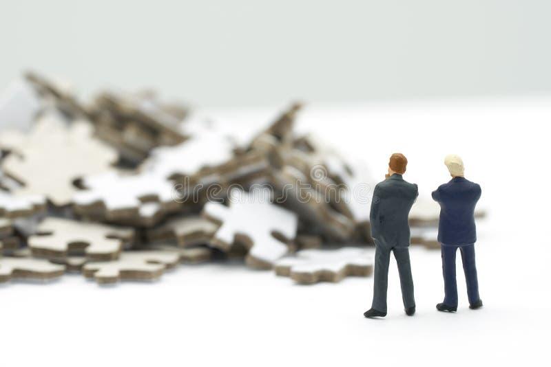 De miniatuurmensenzakenlieden die Investeringsanalyse of investering in Solve bevinden zich brengt in verwarring om een bedrijfso stock afbeelding