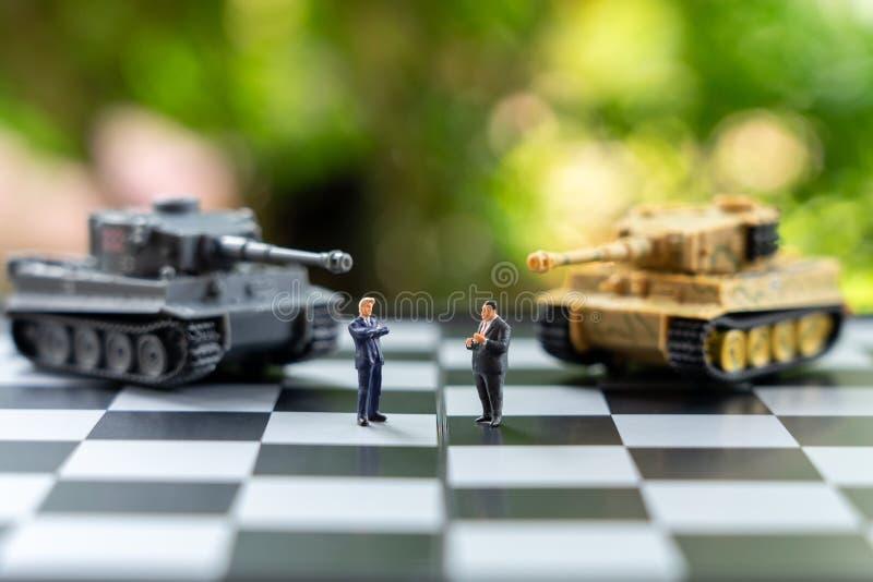 De miniatuurmensenzakenlieden die zich op een schaakbord met een Tank bevinden modelleren op het achter Onderhandelen in zaken Al stock foto
