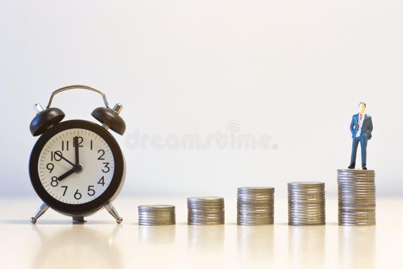 De miniatuurmensenzakenlieden die zich op de stapel van het Geldmuntstuk met wekker bevinden, financieren duurzaam ontwikkelingsc royalty-vrije stock afbeelding
