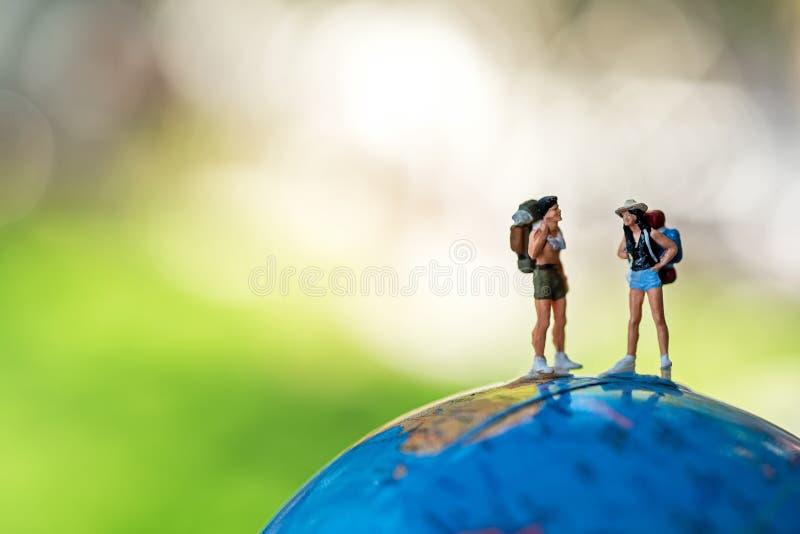 De miniatuurreiziger en wandelaarrugzak die zich op de bol voor de toerist en avontuur rond de wereld voor vakanties bevinden haa stock afbeelding