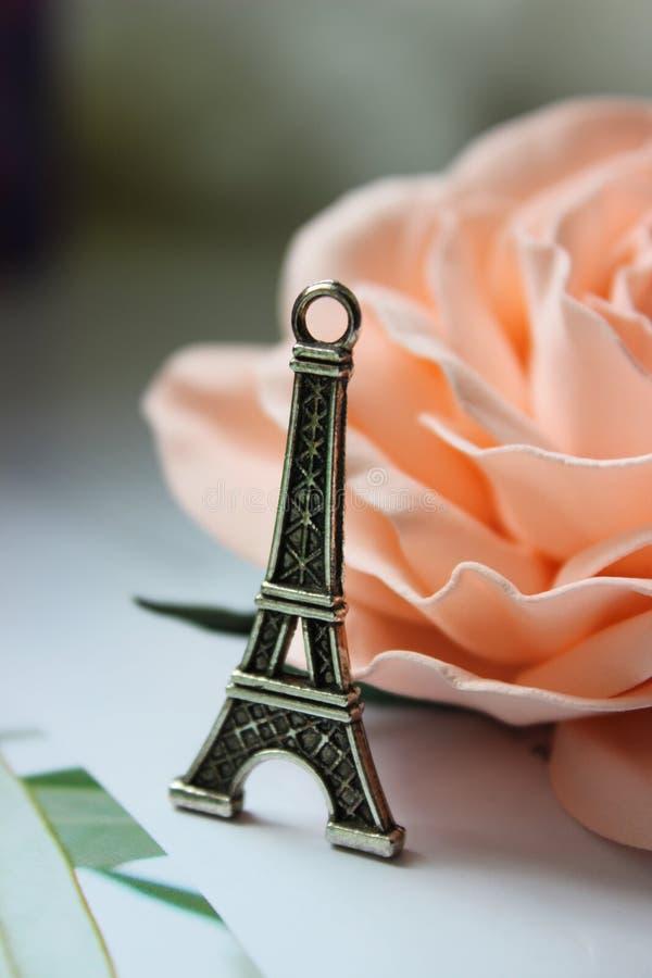 De miniatuurtoren van Eiffel in zilver op de achtergrond van roze bloeien nam toe royalty-vrije stock afbeeldingen