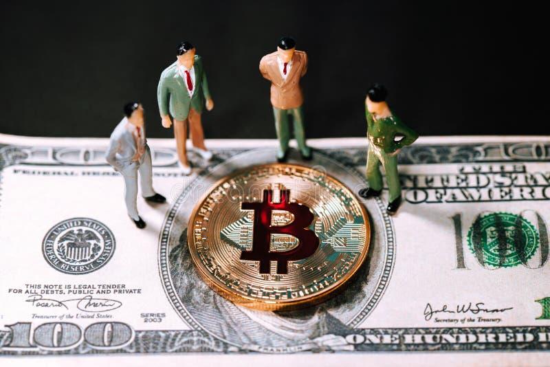 De miniatuurzakenlieden van mensen kleine cijfers bevinden zich en kijkend Gouden bitcoin op honderd dollarbankbiljet stock foto's