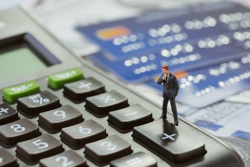 De miniatuurzakenman status op zwarte calculator denkt met zonlicht na op stapel van creditcards en van Amerikaanse dollarrekenin stock fotografie