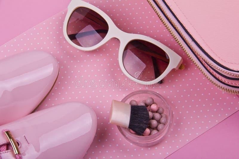 De minimale reeks van mooie vrouwen maniertoebehoren op een roze stippenachtergrond stock foto