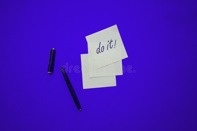 De minimale samenstelling op een kleurrijke pastelkleurachtergrond met woord 'doet het 'geschreven op het weinig document stock foto