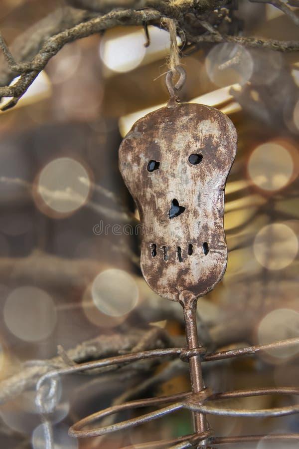 De minimalistische decoratie van Halloween van het metaalskelet hangt van een dode boomtak in vage bokeh atmosfeer stock foto