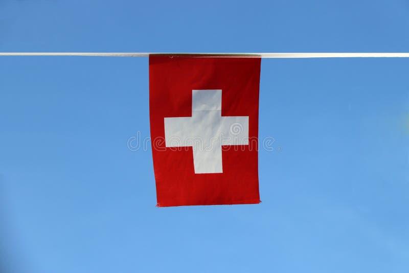De minivlag van het stoffenspoor van Zwitserland, het is bestaat uit een rode vlag met een wit kruis in het centrum, die op de ka stock foto