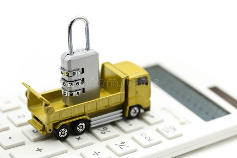 De minivrachtwagen en metaalsleutel van het veiligheidsslot op calculator stock fotografie