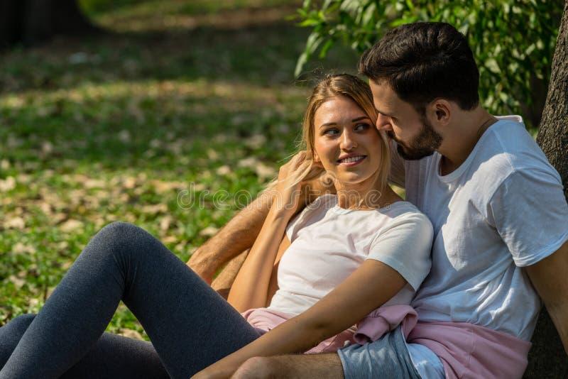 De minnaar zit samen in de openbare holding van de parkmens met zijn meisje met het gelukkige glimlachen royalty-vrije stock foto's