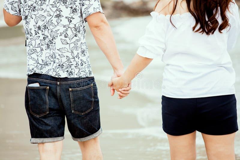 De minnaars koppelen holding handen en samen het lopen op het strand royalty-vrije stock afbeelding