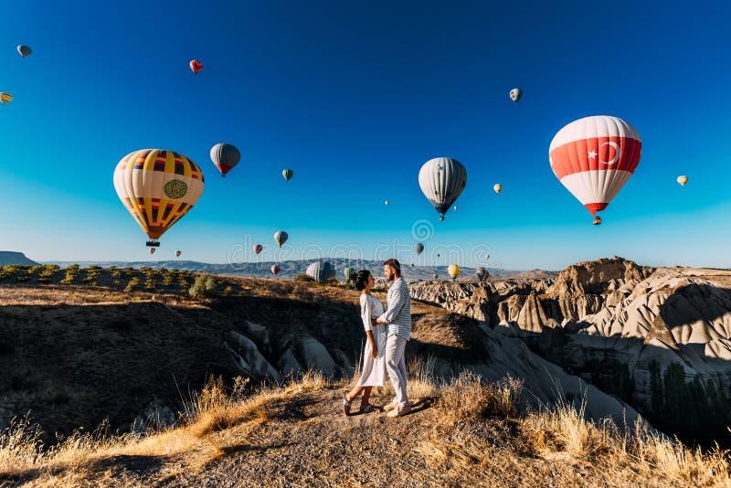 De minnaars reizen naar Turkije De man stelde aan het meisje voor Familiereis aan Turkije Paar bij het ballonfestival Wittebroods stock afbeeldingen