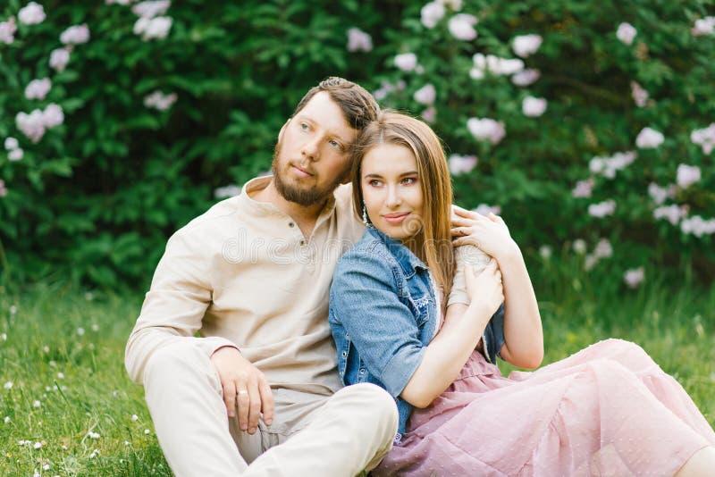 De minnaarsjonggehuwden op een romantische datum zitten op het gras in de lente stock afbeelding