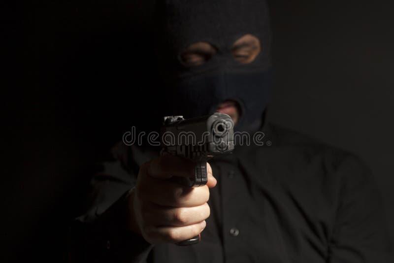 De misdadige bandietenmens die in balaclava dragen houdt een kanon in zijn hand stock foto's