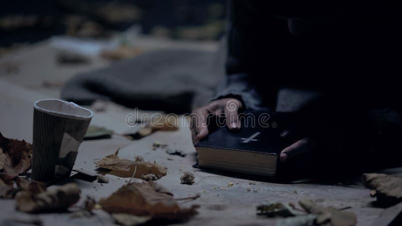 De miserabele bijbel van de zwerverholding en het bidden aan God, sterke overtuiging, geloof royalty-vrije stock fotografie
