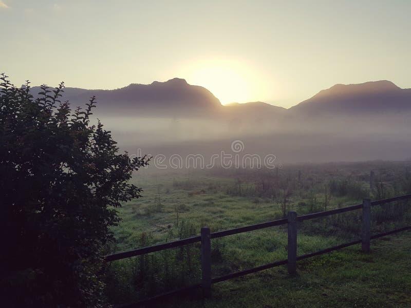 De mistige zonsopgang die van het land bergen overzien stock foto