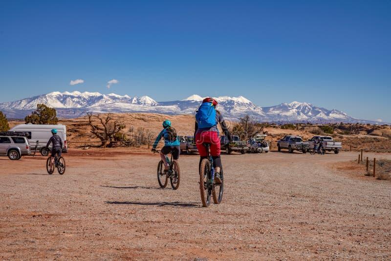 3/16/19 de Moab, Utá Um grupo de pessoas que prepara-se para biking de montanha longo do dia para fora em Moab, Utá imagem de stock