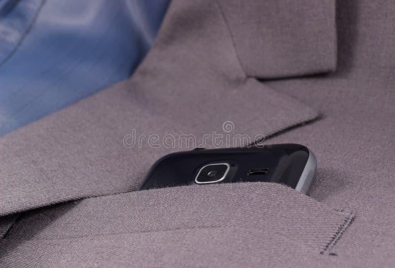 De mobiele camera kijkt uit zijn jasjezak royalty-vrije stock afbeeldingen