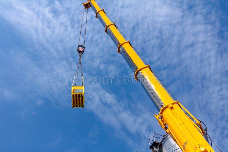 De mobiele kraan heft lading in het werkplatform op, mand stock afbeelding