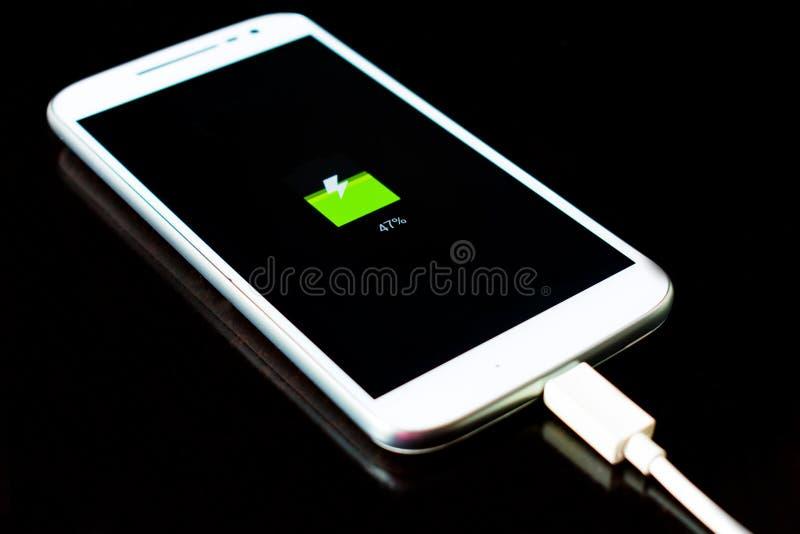 de mobiele telefoon laadt op een zwarte achtergrond stock afbeeldingen