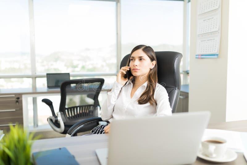 De Mobiele Telefoon van bankiersdoing business on stock afbeelding