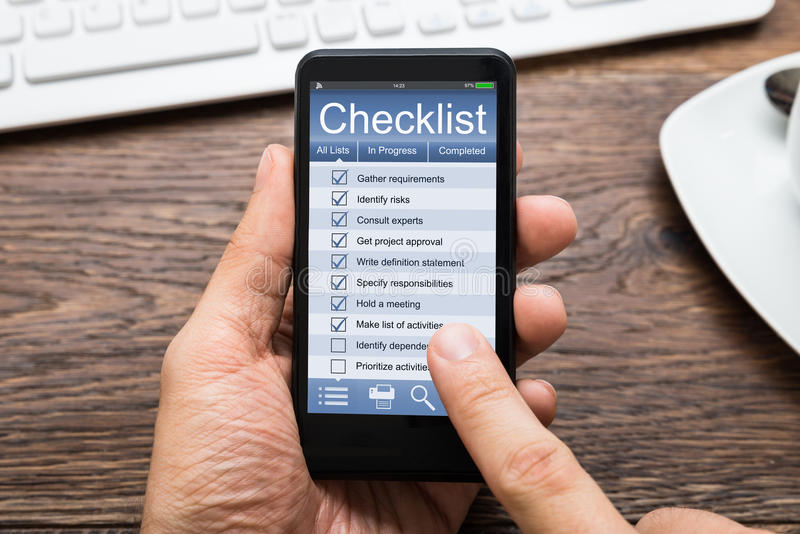 De Mobiele Telefoon van Person Hands Filling Checklist On stock foto