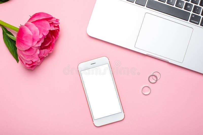 De mobiele telefoonspot en de pioenbloem op roze pastelkleurlijst in vlakte leggen omhoog stijl Vrouwen werkend bureau De zomerkl stock afbeelding