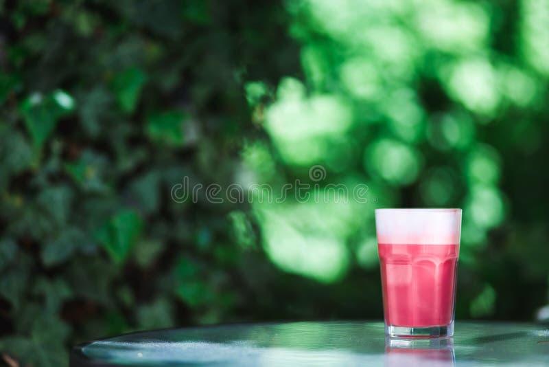 De moda, café del inconformista Un vidrio de capuchino rosado de la fresa en el fondo verde de las hojas Humor del resorte fotografía de archivo libre de regalías