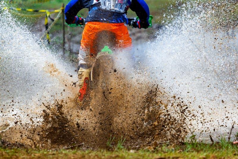 De modder van de Enduromotocross, Motocrossraceauto in een nat en modderig terrein die de bestuurder volledig omvatten stock foto's