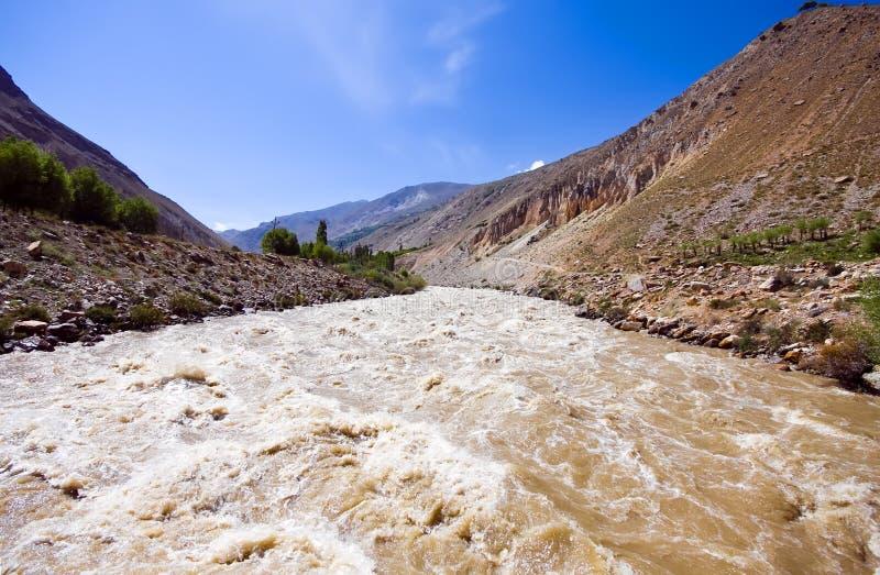 De modderige rivier van de berg onder blauwe hemel stock foto's