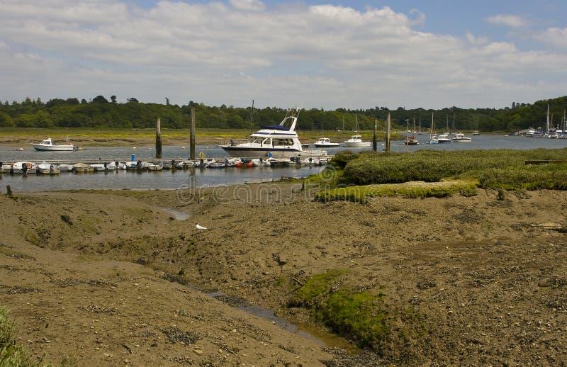 De moddervlakten bij Schilden hard op de Rivier van Beaulieu in Hampshire, Engeland at low tide met boten op hun meertrossen royalty-vrije stock foto