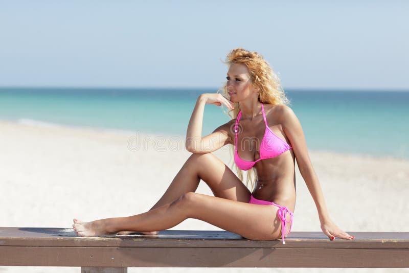 De modelzitting van de bikini op een richel stock foto's