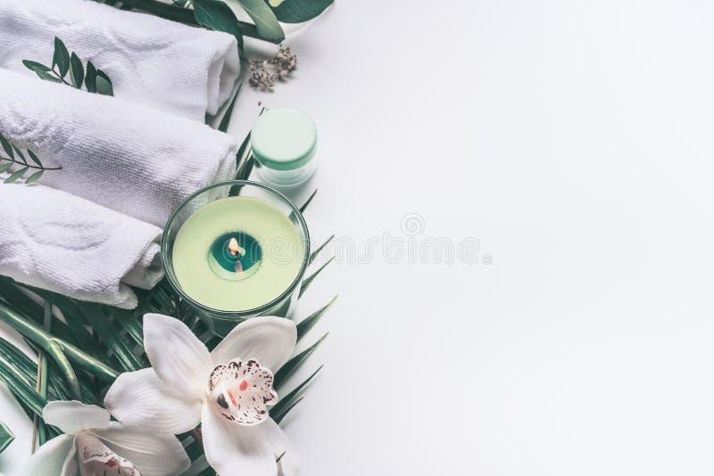 De Modern spa achtergrond met witte handdoeken, hulpmiddelen en groene kruiden, orchidee bloeit, kaarsmateriaal, hoogste mening,  stock foto