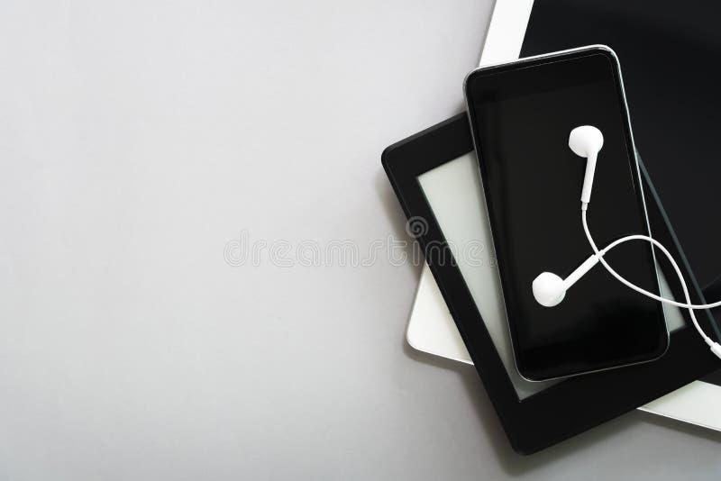 De moderne apparaten, mobiel, de tablet, laptop en de oortelefoon van de verbindingstechnologie op lijst met beschikbare ruimte v stock foto's