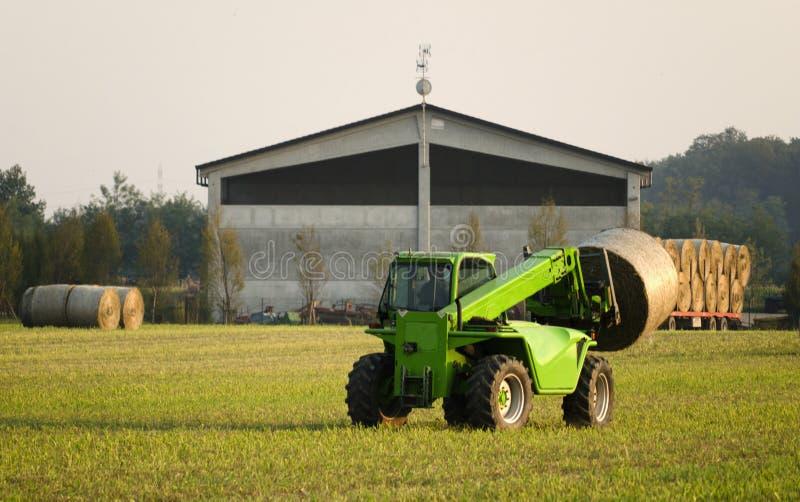 De moderne balen van het tractor bewegende hooi stock afbeelding