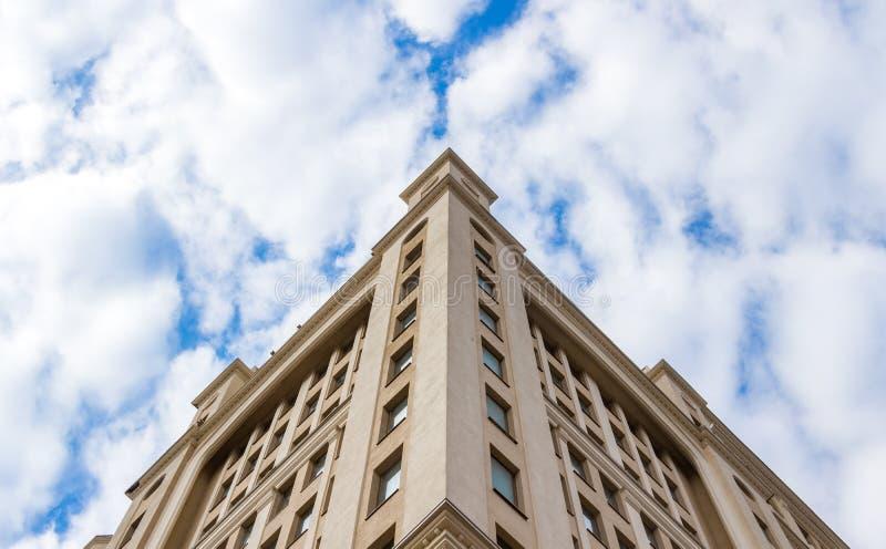 De moderne bouw met meerdere verdiepingen op een blauwe hemelachtergrond stock foto