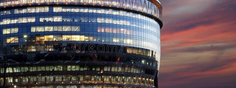 De moderne bureaubouw met grote vensters bij nacht royalty-vrije stock afbeelding