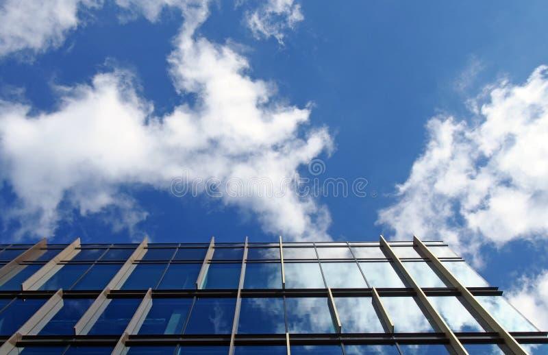 De moderne bureaubouw met weerspiegelde glasvensters die op een heldere blauwe hemel en op witte wolken wijzen royalty-vrije stock foto's