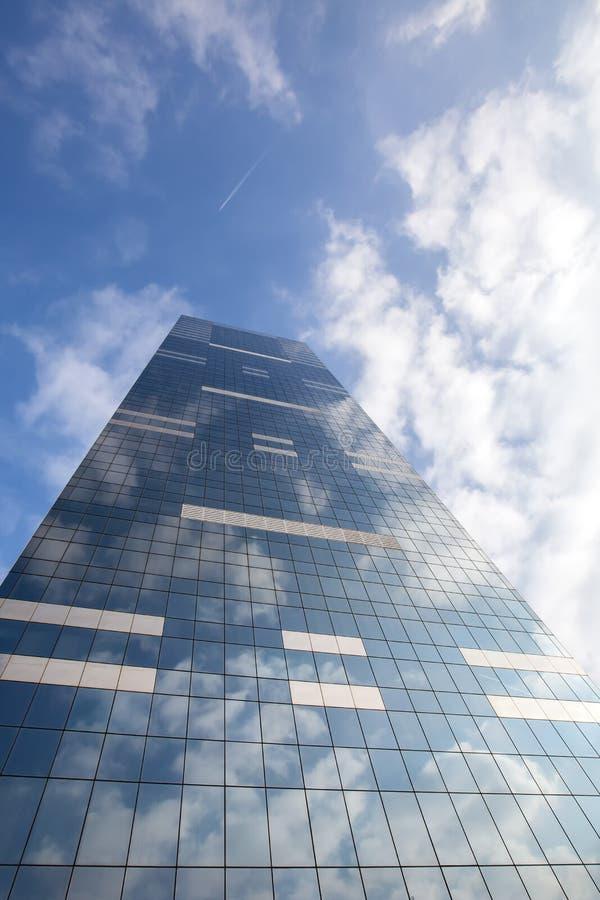 De moderne bureaubouw op hemelachtergrond met wolkenbezinning royalty-vrije stock afbeelding