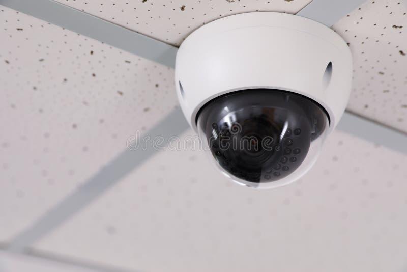 De moderne camera van veiligheidskabeltelevisie op plafond in bureau Beschermingssysteem stock fotografie