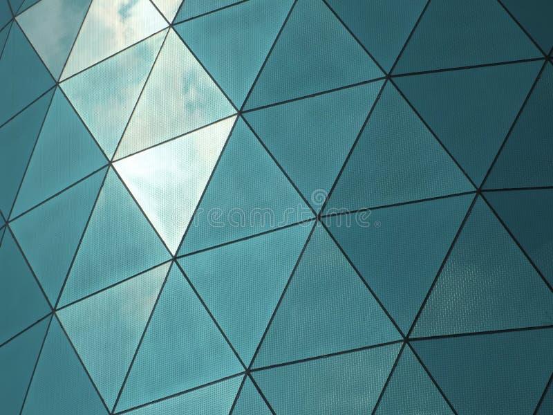 De moderne collectieve bouw met hoekige gevormde weerspiegelde venstersruiten die op de hemel en de wolken wijzen stock foto