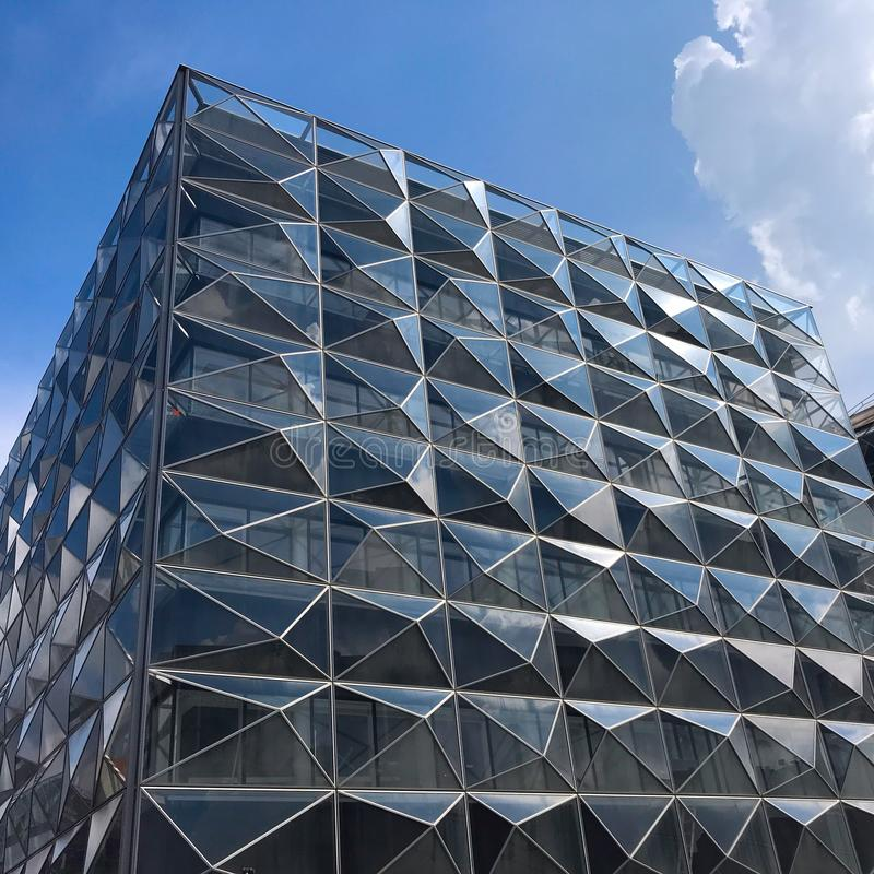 De moderne futuristische bureaubouw met bezinning van wolken en blauwe hemel op de glasvensters royalty-vrije stock afbeeldingen