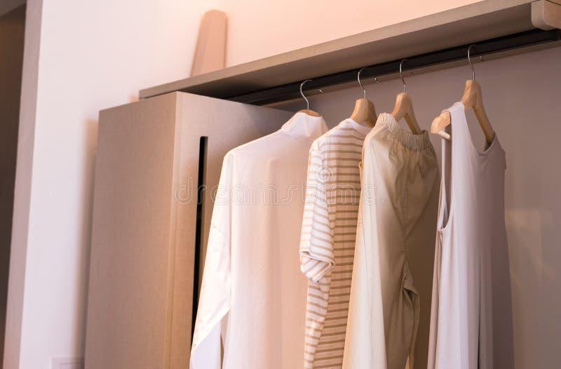 De moderne gang in kasten ontwerpt binnenland met kleren die op spoor warme toon hangen royalty-vrije stock foto's
