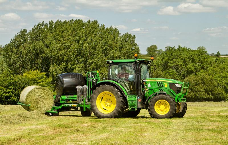 De moderne groene tractor van John Deere met ronde baalomslag stock foto