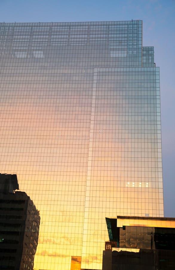 De moderne hoge muur van het de bouwglas in avondtijd Hemelbezinning Bedrijfsdistrictsachtergrond stock foto
