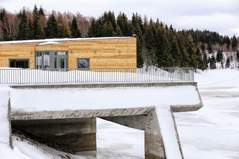 De moderne houten bouw op de concrete brug stock afbeeldingen