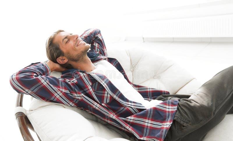 De moderne kerel rust zitting als grote comfortabele voorzitter Zachte nadruk stock afbeeldingen